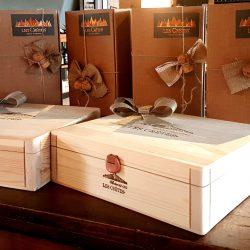 Confezione regalo Les Crêtes: cassette in legno da 3 bottiglie logate e astucci in cartoncino con tappo spumante e nastro.